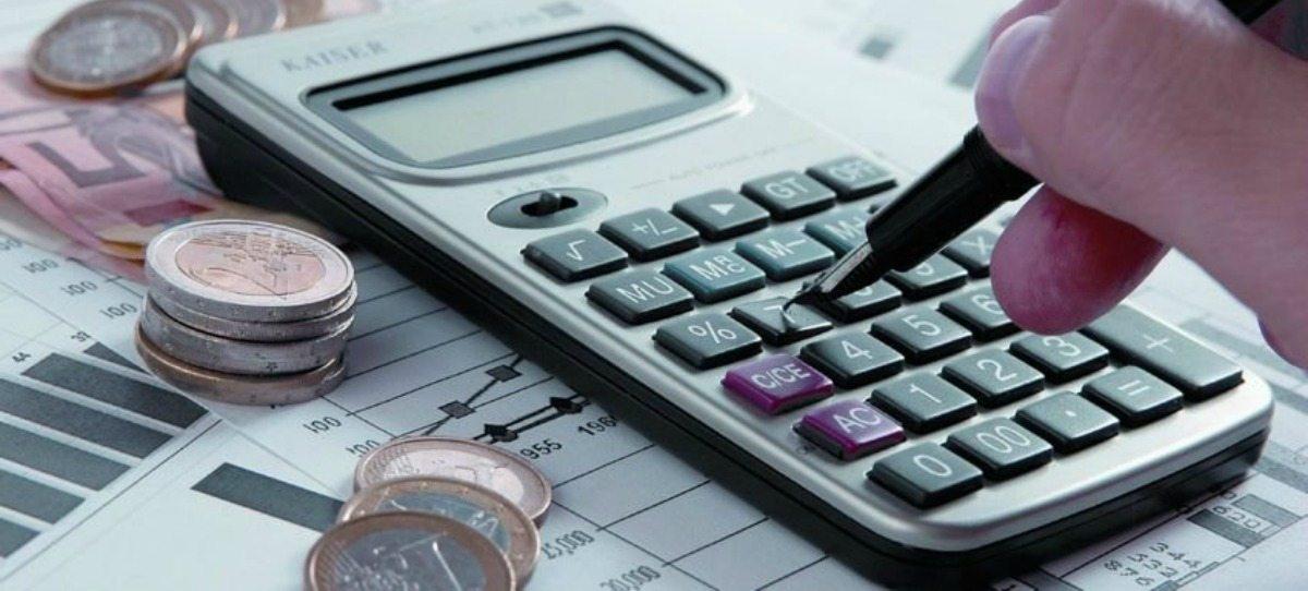 Calculadora junto a unas monedas y sobre unos gráficos