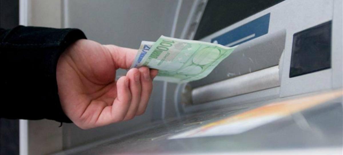 Un hombre saca dinero de un cajero