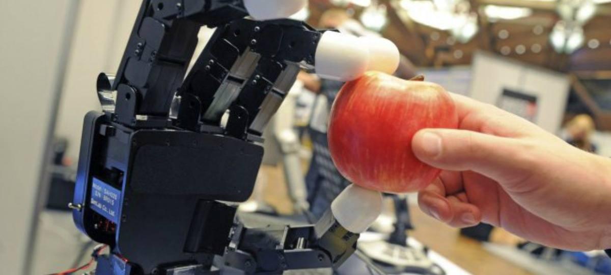 Un brazo robótico coge una manzana